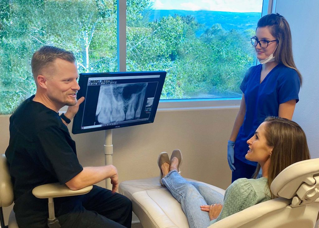 Endodontist and Assistant Showing X-ray results to a patient.